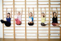 Group of young sports woman does an extension exercise at the Swedish wall Stock Photography