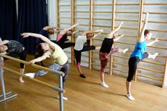 Group of young sports woman does an extension exercise at the Swedish wall Stock Image