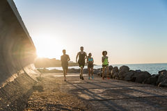 Group of young sporty friends jogging together outdoors Royalty Free Stock Photos