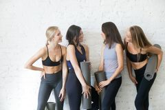 Group of young sporty girls with yoga mats talking. Group of young sporty girls with fitness mats talking. Chatting while having a break, exchanging news Royalty Free Stock Photos