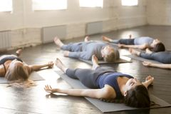 Group of young sporty people in Corpse exercise. Group of young sporty people practicing yoga lesson in gym, lying in Corpse exercise doing Savasana pose royalty free stock photography