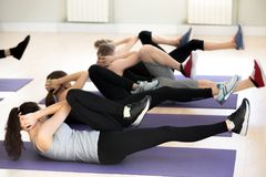 Group of young sporty people doing bicycle crunches stock photos