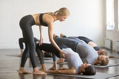 Group of young sporty people in Bridge pose. Group of young sporty people practicing yoga lesson with instructor, stretching, doing Glute Bridge exercise, female Stock Photos