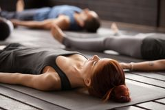 Group of sporty people in Dead Body pose. Group of young sporty people practicing yoga lesson lying in Dead Body or Corpse pose, Savasana exercise, working out Stock Images