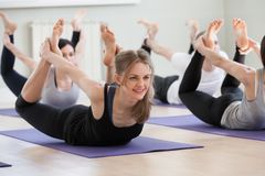 Group of young sporty people practicing yoga lesson, Bow pose. Group of young sporty people practicing yoga lesson, smiling women doing Dhanurasana exercise, Bow stock images