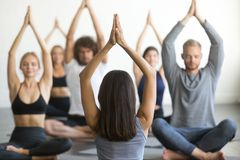 Group of young sporty people sitting in Sukhasana pose. Group of young sporty people practicing yoga lesson with instructor, sitting in Sukhasana exercise, Easy royalty free stock photos