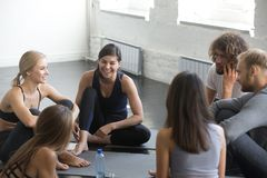 Group of young sporty smiling people talking after yoga class. Group of young sporty smiling people sitting on the floor, yoga practitioners talking after lesson Royalty Free Stock Photos