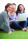 Group of young student  sitting on green grass Royalty Free Stock Images