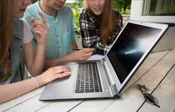 Group of young student using laptop outdoor. Young students outdoors using laptops on a wooden table and connecting to internet, education and learning concept Stock Photography