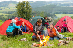 Sitting by campfire friends in tents chatting Stock Photo