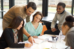 Group of young students studying together. Multiethnic group of young students doing their studies together at a table. Mixed race people in cooperation with Royalty Free Stock Images