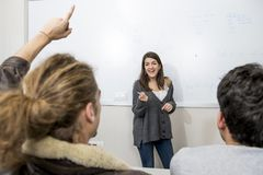 Group of young students taking lesson at University classroom with girl standing on blackboard explaining and pupils sitting on de. Sk in education and lifestyle Royalty Free Stock Photography