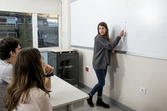 Group of young students taking lesson at University classroom with girl standing on blackboard explaining and pupils sitting on de. Sk in education and lifestyle Stock Photos