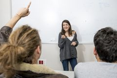 Group of young students taking lesson at University classroom with girl standing on blackboard explaining and pupils sitting on de. Group of young students Royalty Free Stock Photo