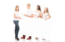 Group of young, stylish and happy teenagers with a banner Royalty Free Stock Photography