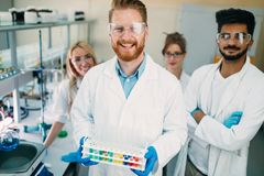 Group of young successful scientists posing for camera Royalty Free Stock Photography