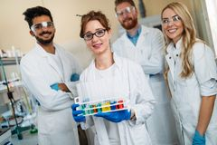 Group of young successful scientists posing for camera. In laboratory Royalty Free Stock Photos