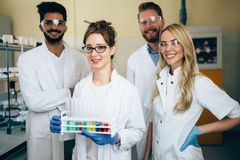 Group of young successful scientists posing for camera. In laboratory Royalty Free Stock Photo