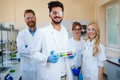 Group of young successful scientists posing for camera. In laboratory Stock Images