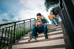 A group of young or teen asian student in university. Smiling and reading the book and look at the tablet or laptop computer in summer holiday Royalty Free Stock Images