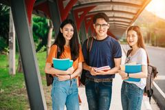 A group of young or teen Asian student in university. Smiling and reading the book and look at the tablet or laptop computer in summer holiday Royalty Free Stock Image