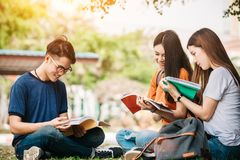 A group of young or teen asian student in university. Smiling and reading the book and look at the tablet or labtop computer in summer holiday Royalty Free Stock Image