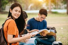 A group of young or teen Asian student in university. Smiling and reading the book and look at the tablet or laptop computer in summer holiday Royalty Free Stock Photography