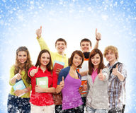 A group of young teenagers holding thumbs up. A group of young and happy Caucasian teenagers holding notebooks and thumbs up. The image is taken on a light blue Stock Image