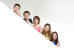 A group of young teenagers holding a white banner Royalty Free Stock Image