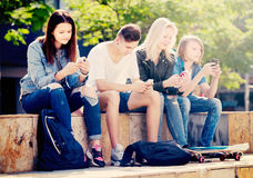 Group of young teenagers sitting with phones Royalty Free Stock Photography