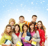 A group of young teenagers on a snowy background. A group of young and happy Caucasian teenagers in modern clothes hanging out together. The image is taken on a Stock Images