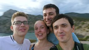 A group of young tourists makes a selfie video on nature. stock footage