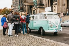 Berlin, October 1, 2017: Group of young unknown tourists book tourist trip on blue retro mini bus next to the Berlin Stock Images