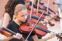 Group of young violinists playing at an outdoor concert Royalty Free Stock Photography