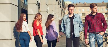 Group of young woman flirting with men in city. Stock Images