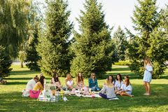 Group of young womans sit on picnic blanket in green summer park. Summer weekends royalty free stock photography