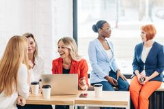 Group of young women discussing creative project during work process royalty free stock photos