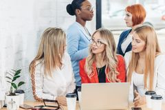Group of young women discussing project during work process with laptop. Group of young modern women in bright colourful casual wear discussing topics while stock images