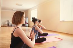 Group of young women doing meditation in yoga class. Tint royalty free stock photo