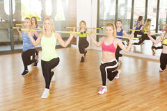 Group of young women in the fitness class, lunges with barbells Stock Image