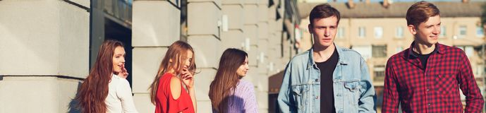 Group of young woman flirting with men in city. Royalty Free Stock Image