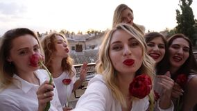 Group of young women are hanging out on a terrace, having fun, lauging. Posing for camera, taking selfie. All in a white stock video
