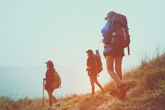 Group young women of hikers walking with backpack on a mountain at sunset. Stock Photo