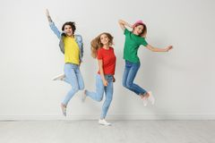 Group of young women in jeans and colorful t-shirts. Jumping near light wall royalty free stock images