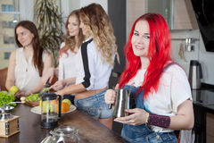Group of young women in a kitchen room preparing. Food Royalty Free Stock Photos