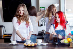 Group of young women in a kitchen room preparing Royalty Free Stock Image