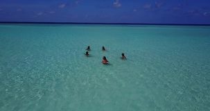 Group of 5 young women playing ball with view from aerial drone on sunny island white beach blue sea sky water Stock Images