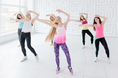 Group of young women posing with arms raised while having a fitness dance class stock image