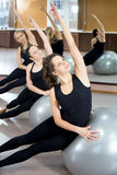 Group of young women practice on pilates fitballs Stock Photos