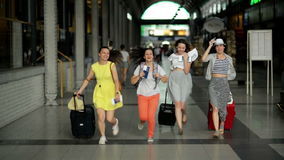 Group of Young Women Running inside the Airport with Documents, Tickets, and Large Suitcases in Hands. Pretty Girls are stock video footage